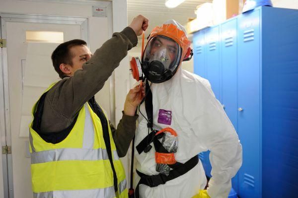 Équipement des opérateurs sur un chantier de désamiantage : scotchage de la jonction appareil de protection respiratoire / combinaison afin d'améliorer l'étanchéité