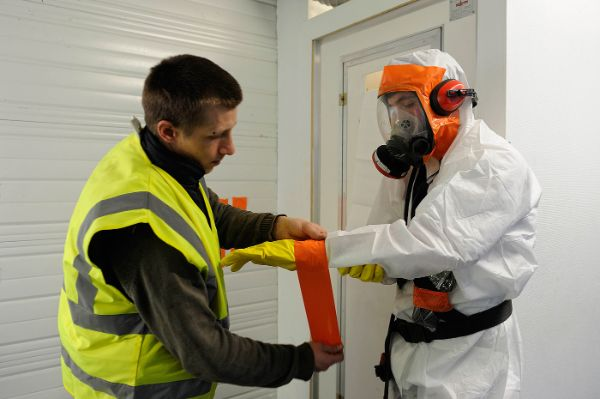 Équipement des opérateurs sur un chantier de désamiantage : scotchage des gants avec la combinaison afin d'améliorer l'étanchéité de la protection individuelle