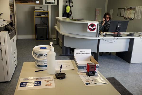Aménagements dans le bureau d'accueil d'une entreprise : signalétique, distributeur de gel hydroalcoolique